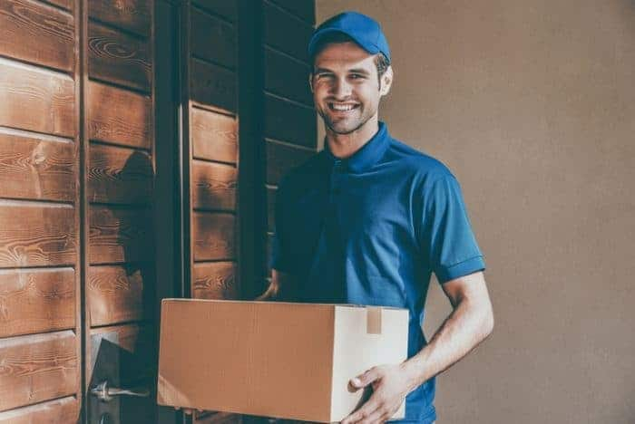 A smiling delivery man holding a parcel in his hands
