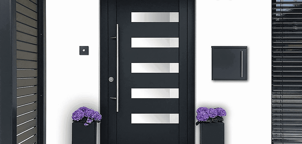 An iLoveParcels letter box mounted to a white wall next to a black foor with some purple flowers to either side