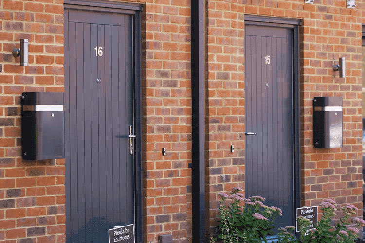 Two black letter boxes mounted on the wall in front of two doors