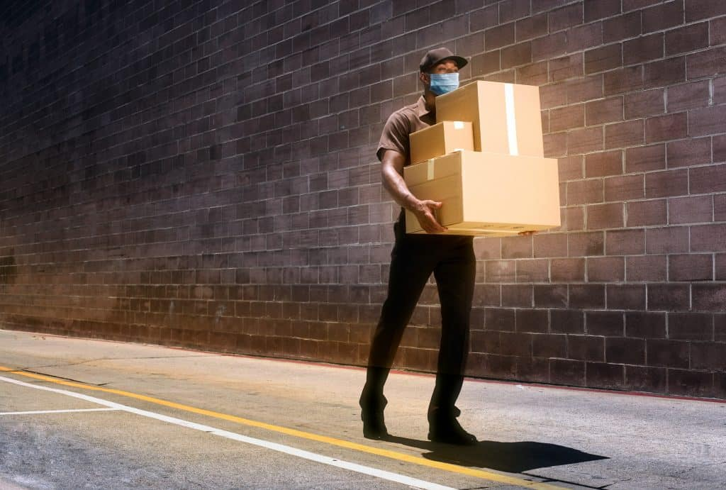 A delivery man carrying three parcels wearing a face mask